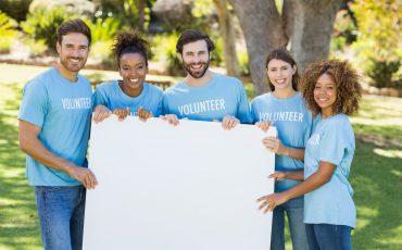 Portrait of volunteer group holding blank sheet
